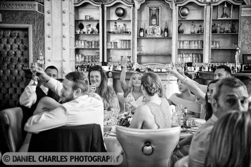 black and white wedding photo of guests laughing at speeches