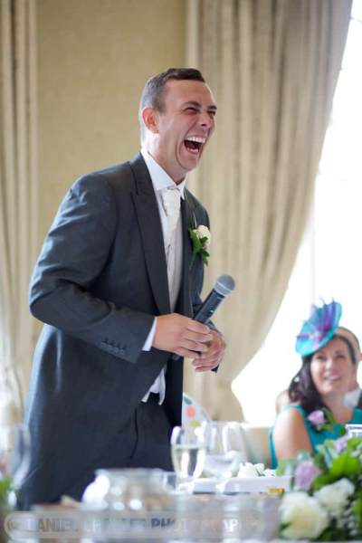 groom laughing  at hecklers during his speech