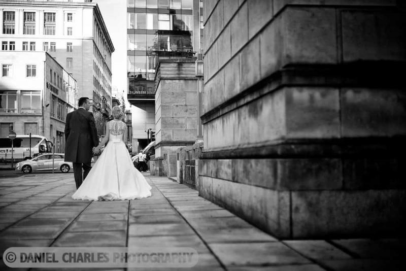 bride and groom walking on pavement. Black and white liverpool wedding photograph