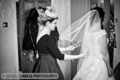 black and white wedding photo of bride having veil adjusted