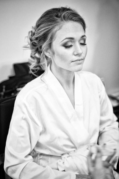 a bride closes her eyes before makeup is applied