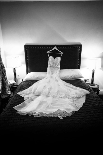 wedding dress is draped across a double bed in the racquet club
