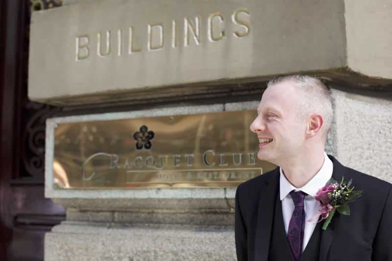 a groom smiles outside the racquet club liverpool