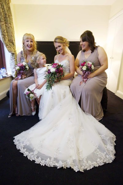 bride and bridesmaids seated on a bed in the racquet club
