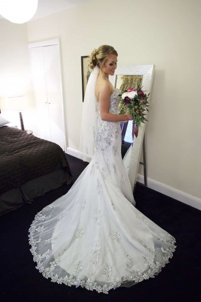 a bride stands in front of a mirror, holding her flowers