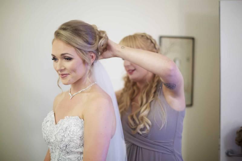 bridesmaid attaches a wedding veil to the bride's head