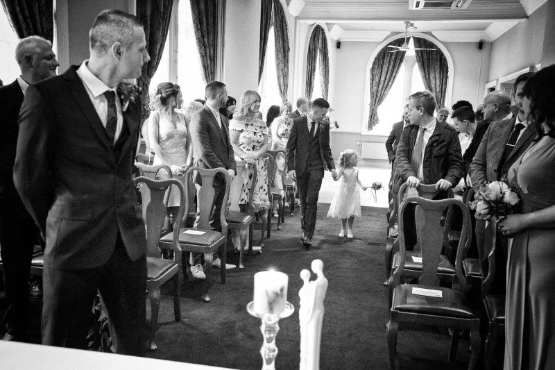 the wedding party looks on as an usher helps the flowergirl along the aisle