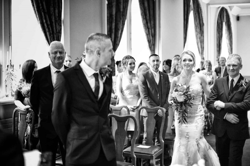 bride and her father approach the groom, who has turned to look