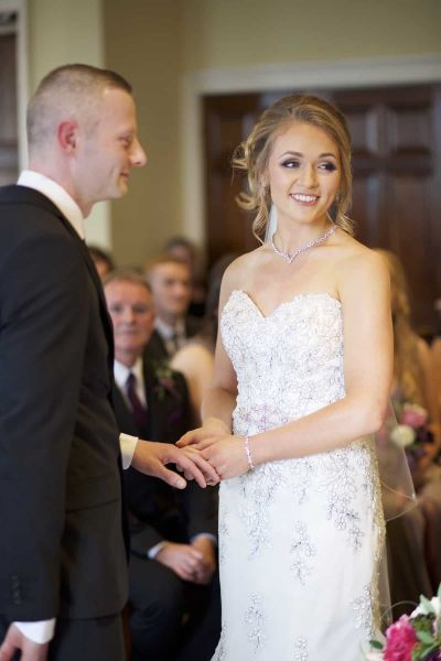 the bride places the ring on the groom's finger