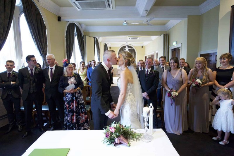 a bride and groom kissing in front of their guests at their racquet club wedding