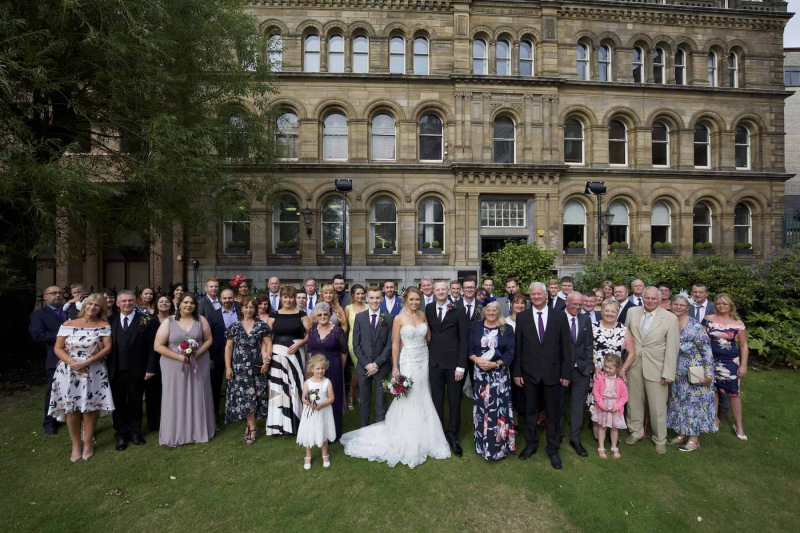 all the wedding party group standing  in a park