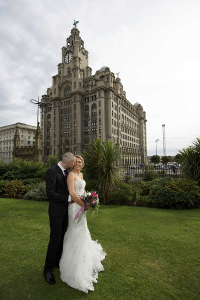 Groom kissing bride with liver building in the background