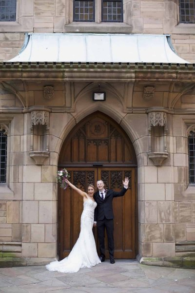 a bride and groom waving from the door of the church