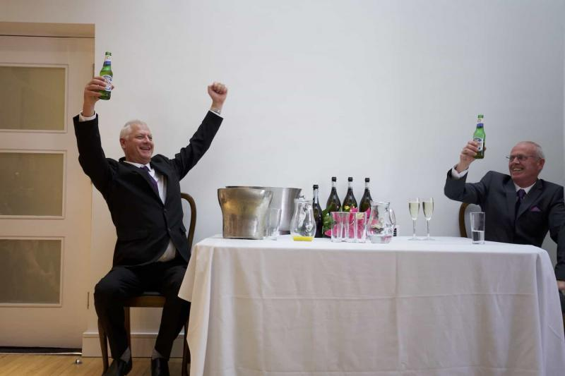 father of the groom raises his arms in celebration