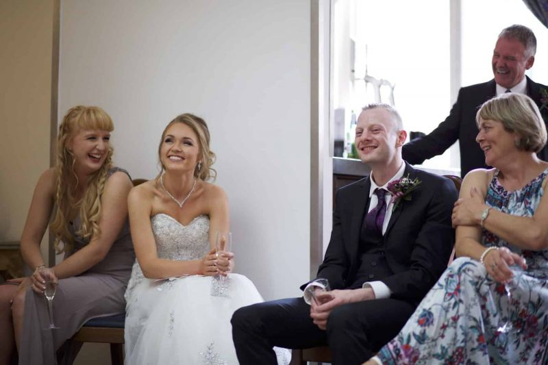 wedding party laughing at best man's speech