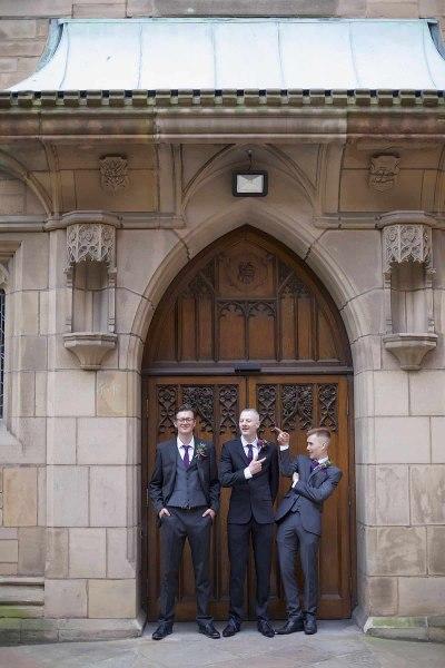 groom and  groomsmen larking around outside church