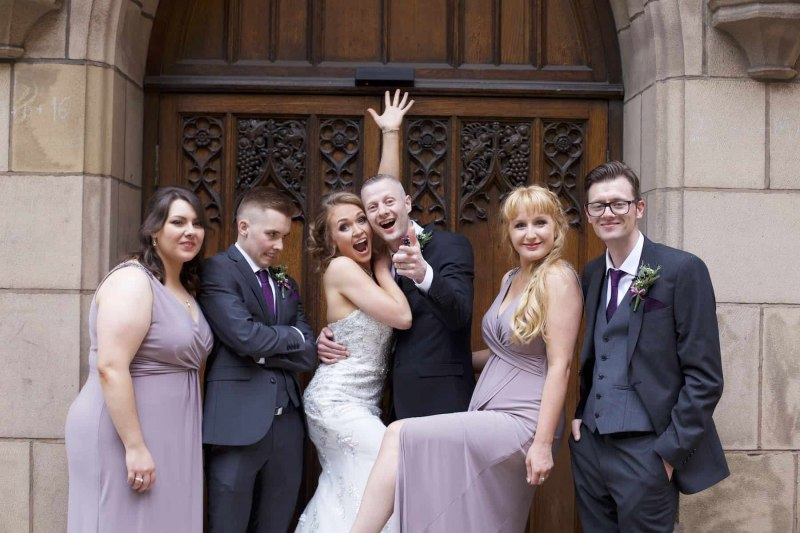 bridal party larking around outside church