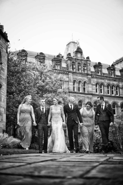 bridal party walking hand in hand through gardens in liverpool