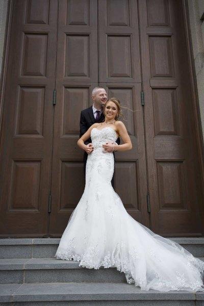 bride and groom standing on steps outside huge door in liverpool