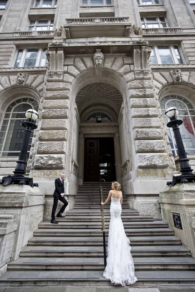 bride and groom standing on steps of the cunard Building in Liverpool