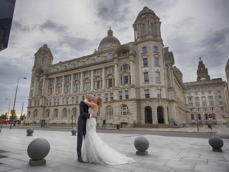 bride and groom kissing in front of Port of Liverpool building