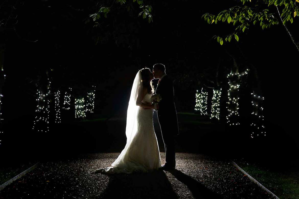 bride and groom kissing in the dark