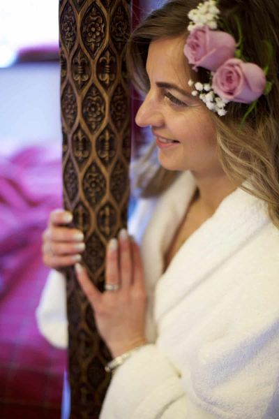 a bridesmaid leans against an ornately carved post of a four poster bed