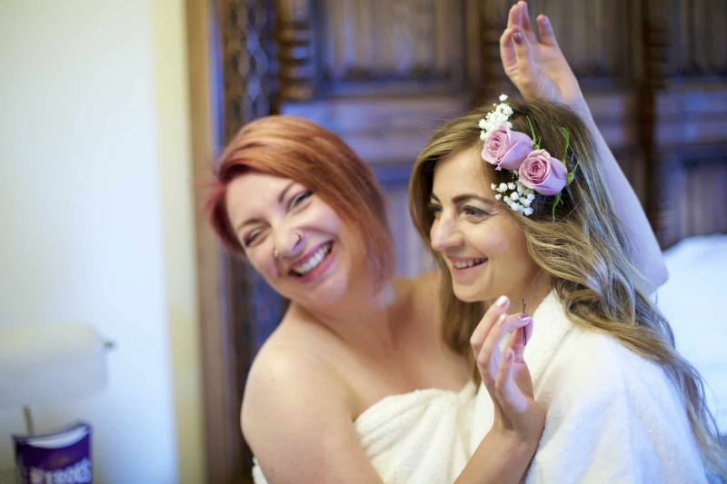 A bride and her bridesmaid are laughing together in the wedding preparation room