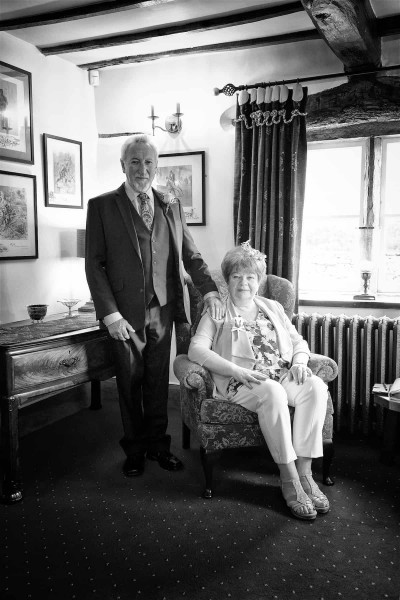 A black and white photograph of a man standing and a seated woman in a lounge