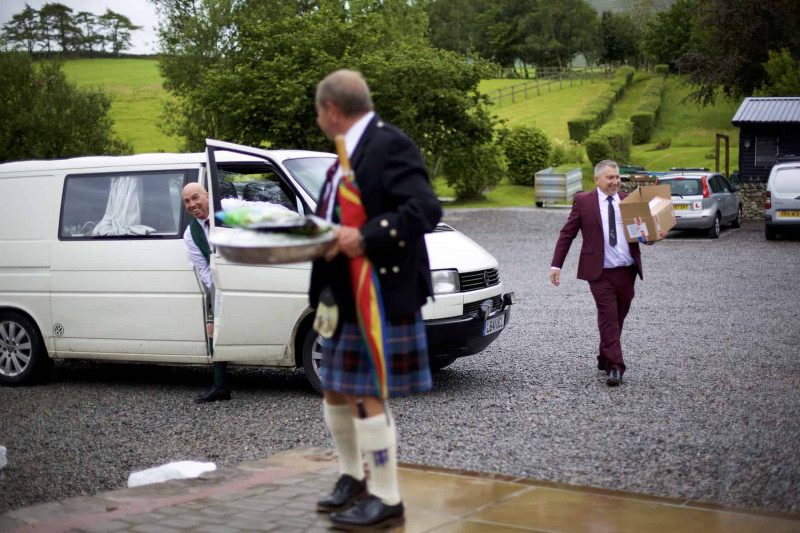 A camper van arrives with the groom and his groomsmen