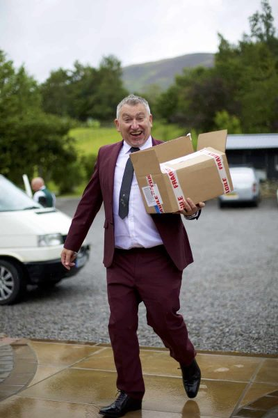 The groom is holding a cardboard box full of orders of service