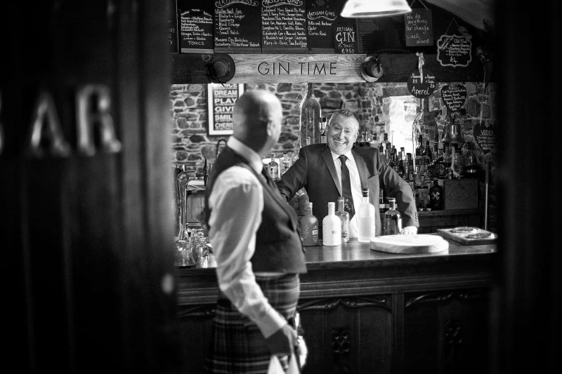 A black and white photograph of a groom standing behind a bar with his friend looking on