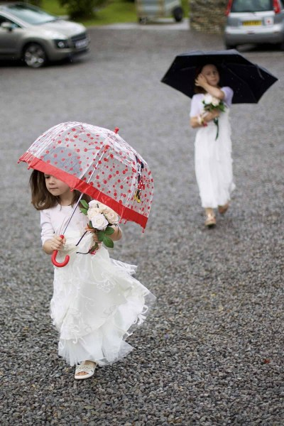 a pair of flower girls arrive at the wedding carrying umbrellas