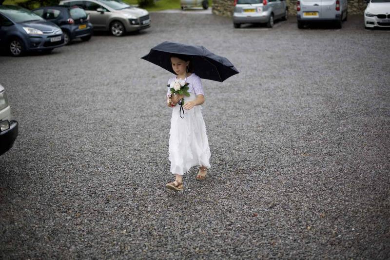 a flower girl arrives at the wedding underneath an umbrella