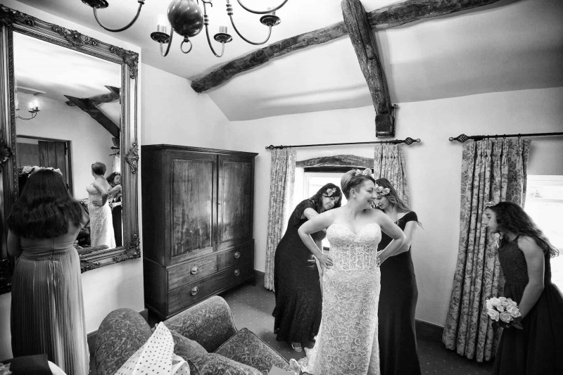 Black and white photograph of a bride's dress being done up by her bridesmaids