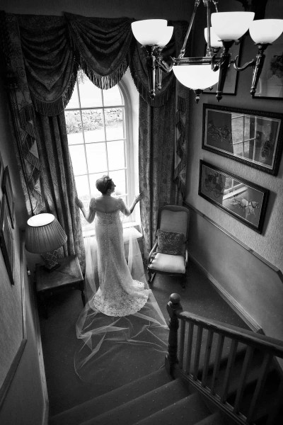 A black and white wedding photo of a bride standing by a window surrounded by furniture