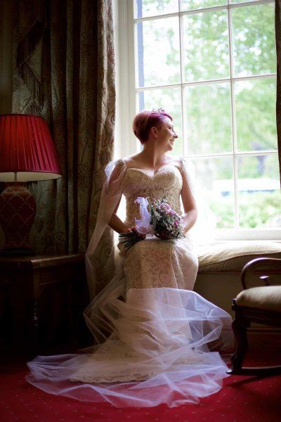 A bride is seated in a bay window, looking out the window