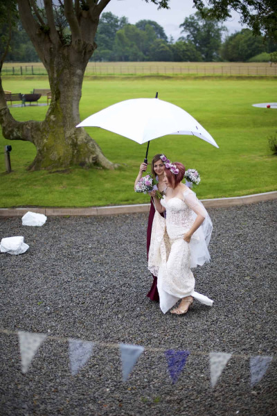 The bride and her maid of honour are walking on a gravel path underneath an umbrella