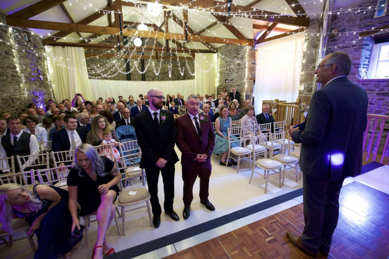 The groom and his best man are waiting for the arrival of the bride in a barn wedding
