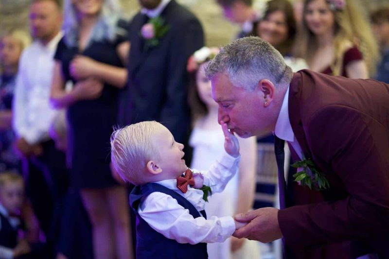 a page boy is  touching the groom's face with his hand