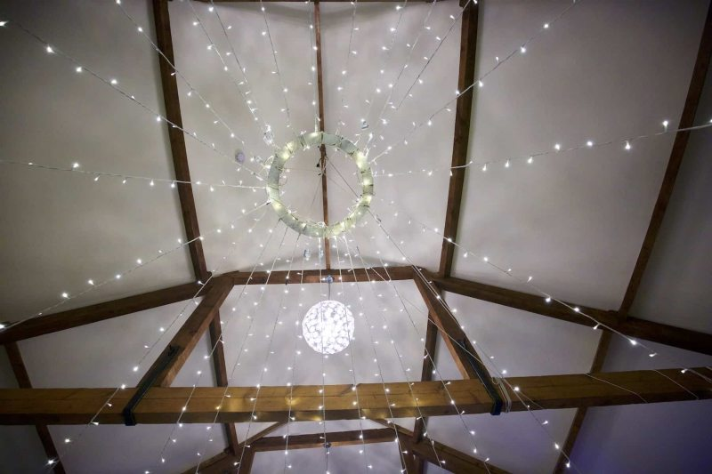 an array of fairy lights hanging from the ceiling of a converted barn