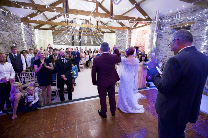 a bride and groom raise their joined hands in celebration with their guests