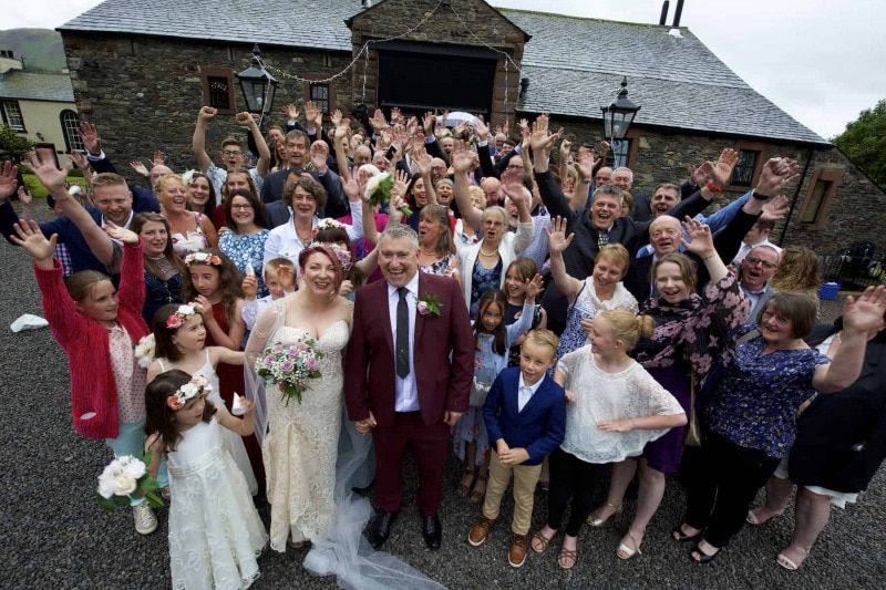 The entire wedding party is gathered together, waving at the camera