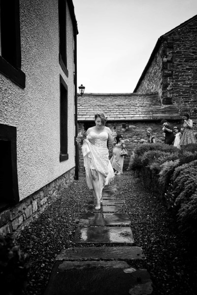 Black and white photograph of  a bride walking along a path