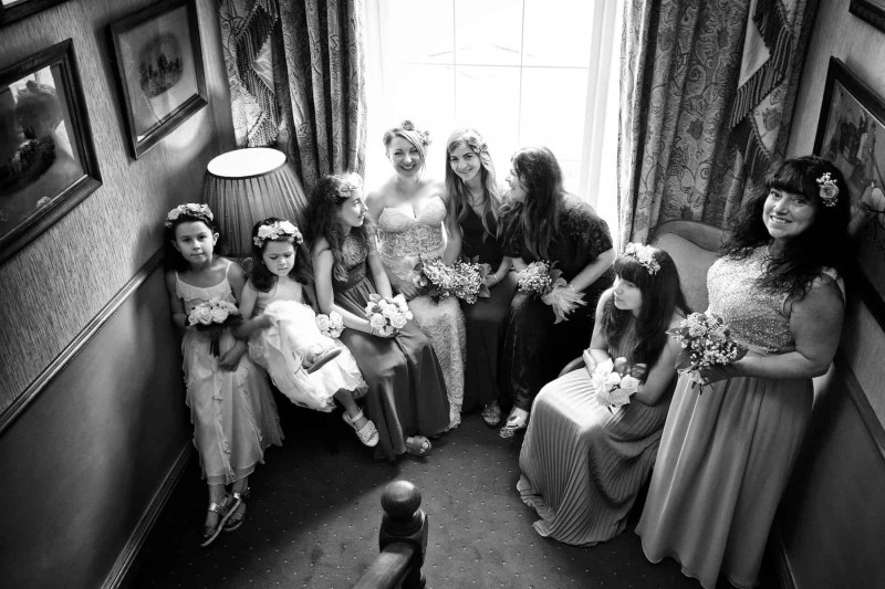 Black and white wedding photograph of the bride and all her bridesmaids. Most are seated.