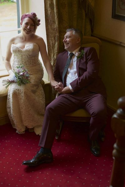 The bride and groom are seated in a bay window, holding hands