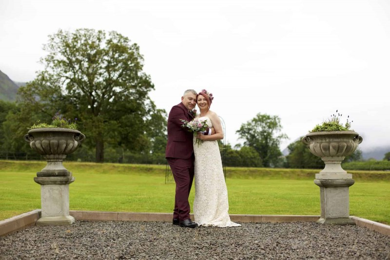 the  bride and groom are standing embracing between two plant pedestals