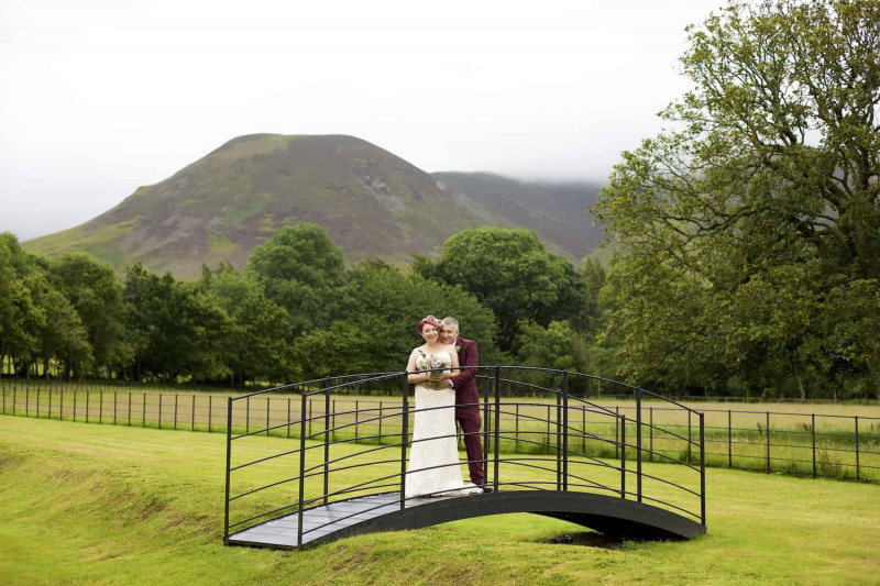 the bride and groom are embracing whilst standing on a bridge over a ditch