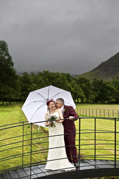A bride and groom are laughing together under a large white umbrella