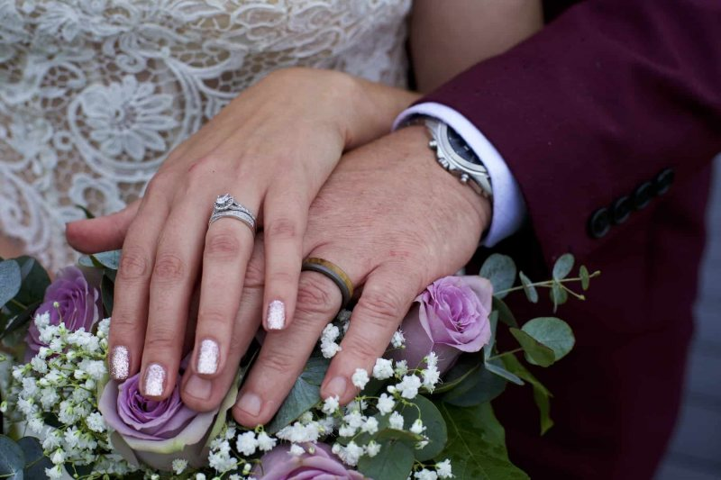 the bride and groom's hands are showing their wedding rings